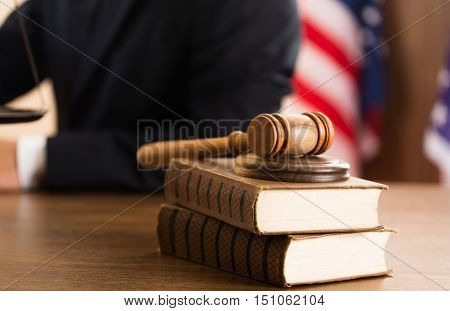Closeup of Gavel and Books with Scale and Lawyer on Background