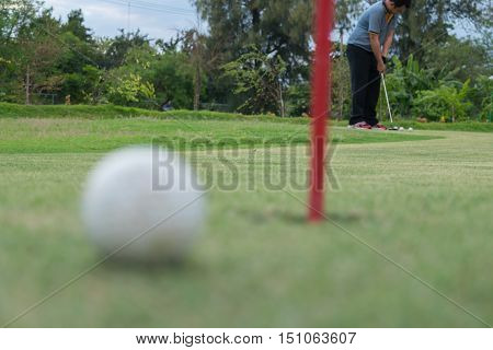 Golf Player And Golf Ball Lip Of Hole On Green