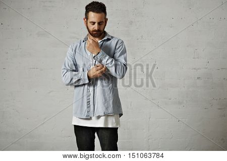 Young bearded man wearing a light blue denim shirt and black jeans unbuttoning his shirt sleeve against a white brick wall background