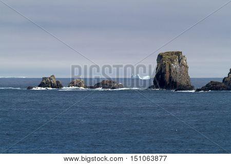Atlantic coastline with rocks, waves and iceberg.