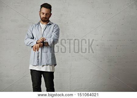Young bearded hipster rolling up a sleeve of his casual light denim shirt showing tattoos on his arm in a studio with white brick walls