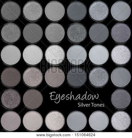 A background palette of eyeshadows in smokey tones of grey and silver.
