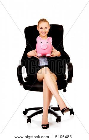 Business woman sitting on armchair and holding piggybank