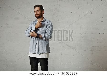 Thoughtful looking hip young model with beard and tattooed arms unbuttoning a sleeve of his light denim shirt isolated on white