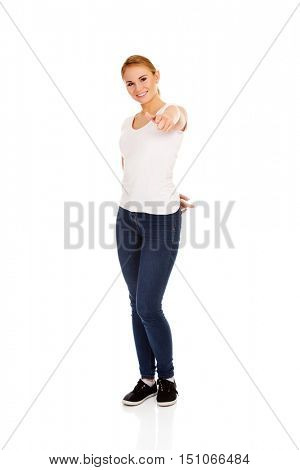 Smiling young woman pointing at camera