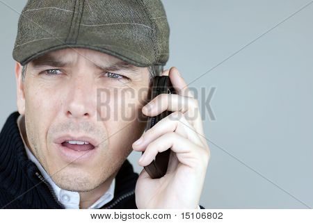 Worried Man In Newsboy Hat On Phone