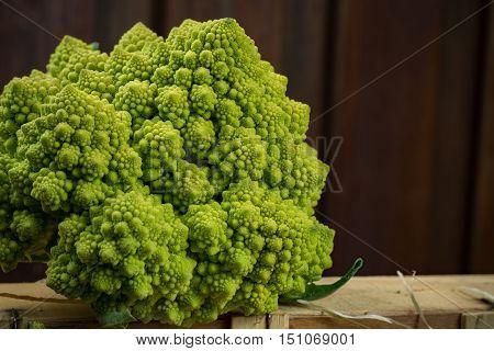 Green Fresh organic Romanesque Cauliflower on wooden background