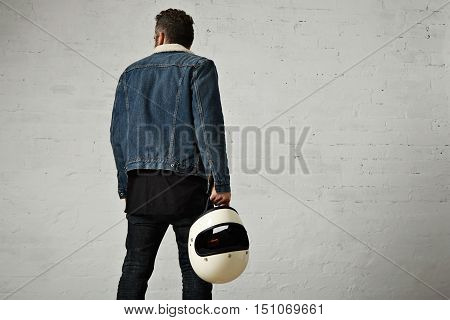 Backside view of brutal young motor biker wears shearling denim jacket and black blank henley shirt, walkinf away and holds vintage beige motorcycle helmet, isolated in center of white brick wall