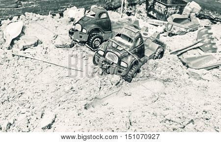 Forgotten of childhood cars in sandbox in black and white