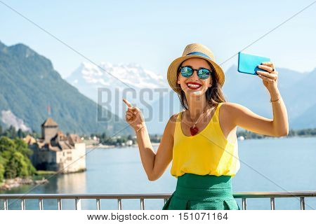 Young female traveler making selfie photo in front of Chillon castle on Geneva lake in Switzerland