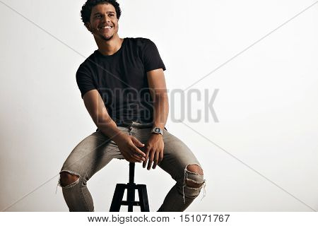 Happy smiling black young man sitting comfortably on a black stool wearing gray jeans and an unlabeled black t-shirt isolated on white