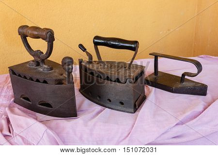 three old irons made of cast-iron on a shirt
