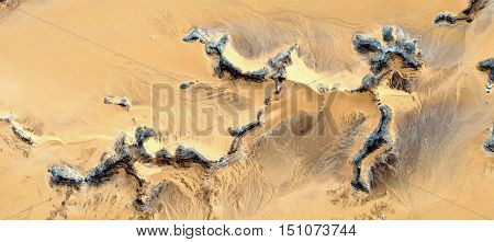 keletons stone, Fossil remains of the first human to try to cross the Sahara Desert seen from the air, in the African desert mirage, yellow background, texture of dark stone, sand texture,