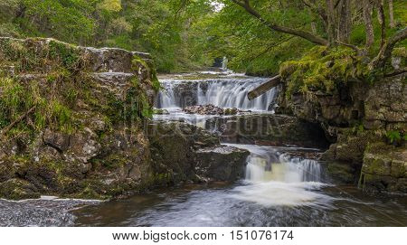 Sgwd Y Bedol waterfall with Ddwl Isaf in the distance on the Nedd Fechan along the Elidir trail in South Wales UK. Long exposure with motion blur
