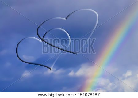 Two silhouette hearts on sky background and rainbow .