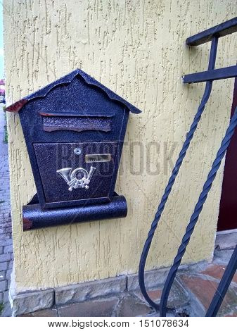 on the street hangs a beautiful metal mailbox on wall
