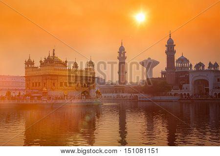 Sikh gurdwara Golden Temple (Harmandir Sahib) on sunrise. Amritsar, Punjab, India. With light leak and lens flare