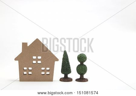 Miniature white house and trees on white background. New house concept.