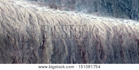 Allegory of waterfall in the desert, mirage in Sahara, abstract surreal photograph from the air,white creamy texture and light tan,white background with turquoise accents