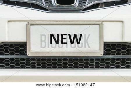 Closeup old license plate at the in front of car for sale textured background with black new word at the center of license plate
