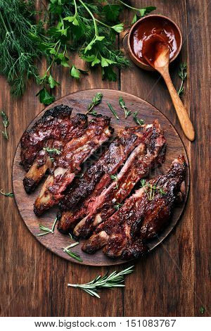 Grilled sliced barbecue pork ribs green herbs and tomato sauce top view