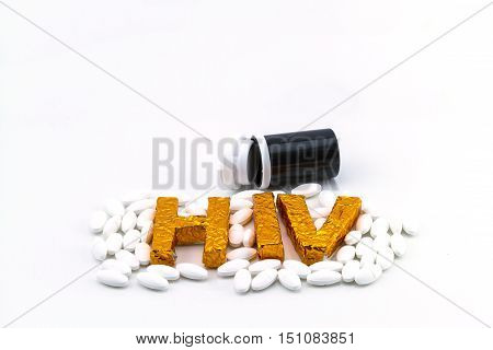 A word HIV on pill lie strewn and black bottle background