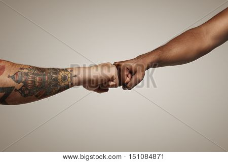 Two men one light skinned with tattoos and another dark skinned do a fist bump against white wall close up