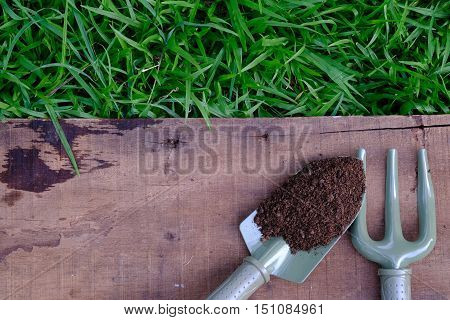 Garden Tools And Peat Moss On Wooden Table Top