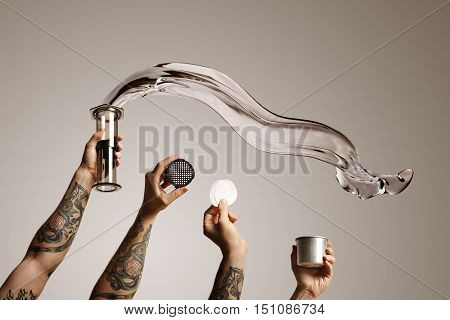 Four tattooed hands holding aeropress and spare parts with water flying out of aeropress on white background Alternative coffee brewing commercial