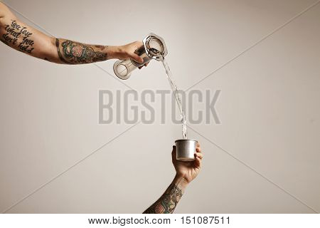 Two tattooed man's hands pouring water from a clear plastic aeropress into a small steel travel cup on white background Alternative coffee brewing commercial