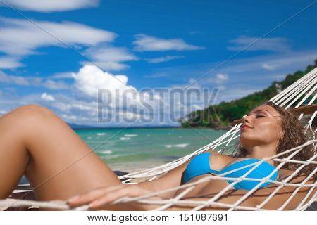 Beautiful woman in bikini in hammock on sunny beach