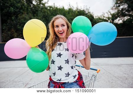Happy young woman having fun with colorful latex balloons outdoors
