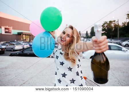 Cheerful young girl holding bottle of champagne and balloons and having a party