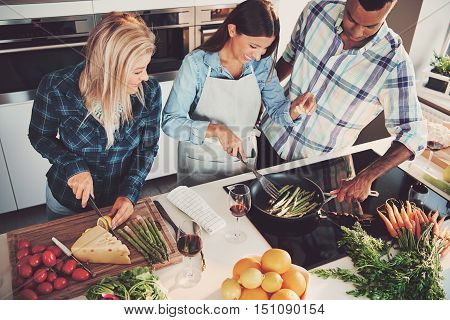 High angle view of trio cooking a meal with tomatoes cheese asparagus fruit and other ingredients on kitchen counter and stove
