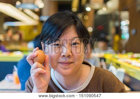 Asia woman plump body holding a egg defocus blurred on BBQ. yakiniku grill buffet restaurant background.