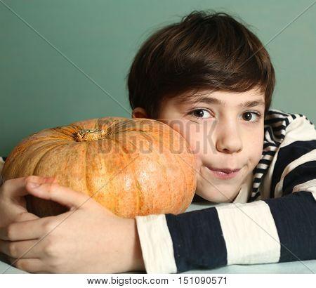 preteen boy with raw whole pumpkin for halloween fest preparation