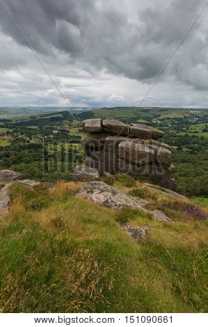Rocks piled up on the edge of a hill at Froggatt Edge in the Peak District Derbyshire