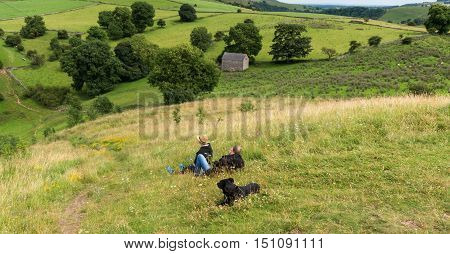 A male and a female and a dog sitting on top of a hillside in the Peak District Derbyshire