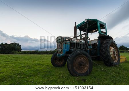 A tractor in a field at sunset in the countrside in the Peak District