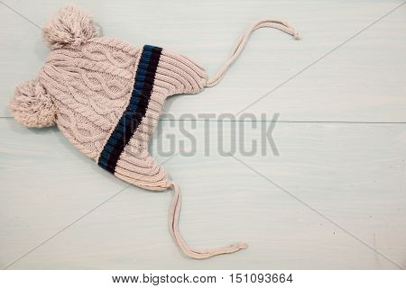 Baby winter warm gloves cone and knitted wool scarf on wooden board. Winter children background. Fashion cozy look of baby clothes on wooden floor baby fashion concept. Little boy clothes set.