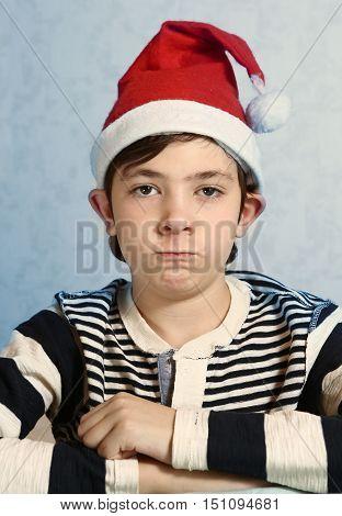 preteen handsome boy in santa hat grimacing acting elf representation
