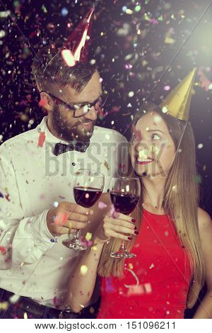 Beautiful young couple in love wearing party hats holding glasses of wine and making a toast