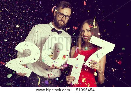 Young couple in love having fun at New Year's party and holding a cardboard numbers 2017