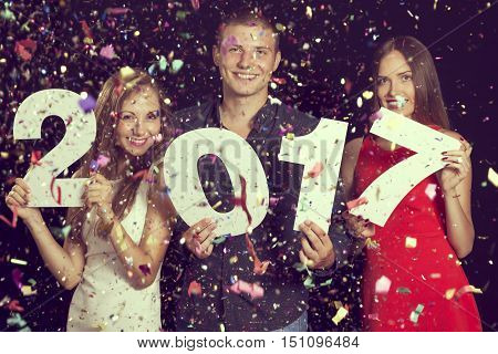 Three beautiful young people enjoying the New Year's party and holding cardboard numbers 2017