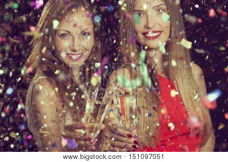Two beautiful young women having fun at a party holding glasses of champagne and making a toast
