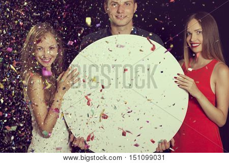 Three young friends having fun at the party and holding a blank cardboard circle