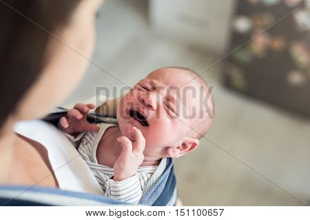 Close up of unrecognizable young mother with her crying newborn baby son in sling at home