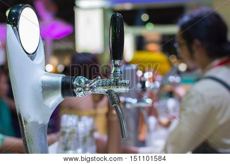 Barman Or Bartender Pouring A Draught Lager Beer From Beer Tap