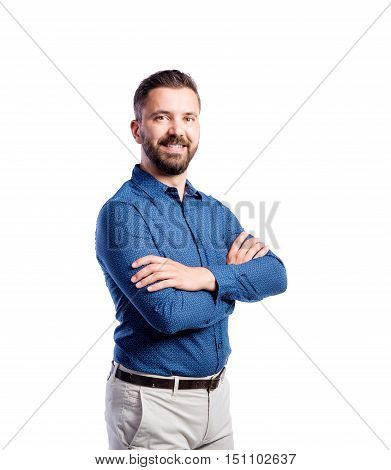 Young handsome hipster man in blue shirt, arms crossed. Studio shot on white background, isolated.