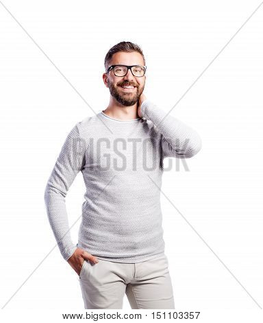 Young handsome hipster man in white long-sleeved t-shirt, hand in pocket. Studio shot on white background, isolated.